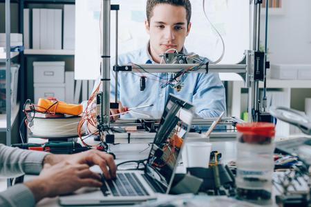 Studenten zitten in het laboratorium bureau en met behulp van een 3D-printer voor prototyping