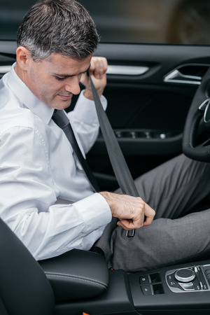 safe driving: Businessman in his car fastening the seatbelt, safe driving concept Stock Photo
