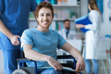 paraplegico: Sonriente joven discapacitado en silla de ruedas en el hospital, un médico le está ayudando Foto de archivo