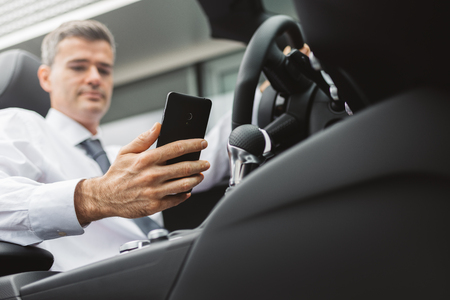 travelling salesman: Businessman searching directions online using apps on his smartphone, car interior