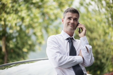 Confident smiling manager having a business call with his smartphone and leaning on his expensive car outdoors Stock Photo