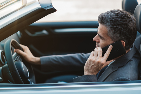 travelling salesman: Businessman driving a luxury convertible car and having business phone calls using his smartphone