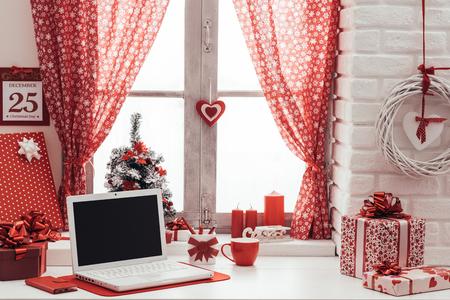 Home interior with red Christmas decorations, calendar and laptop next to a window Banco de Imagens - 65343884