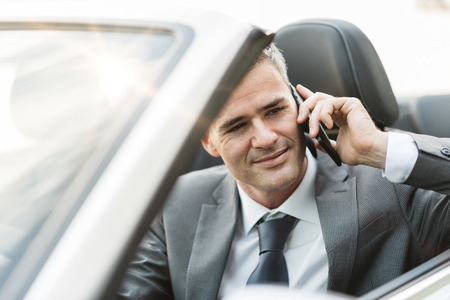 travelling salesman: Confident attractive businessman driving a luxury car and having a phone call with his smartphone
