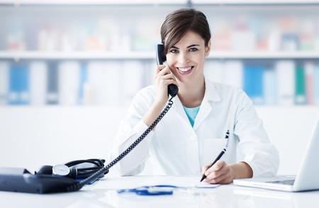 젊은 여성 의사 사무실 책상에서 일하고 응답 전화를 호출합니다.