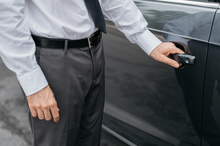 travelling salesman: Businessman opening a car door, hand on handle close up, business and dealership concept