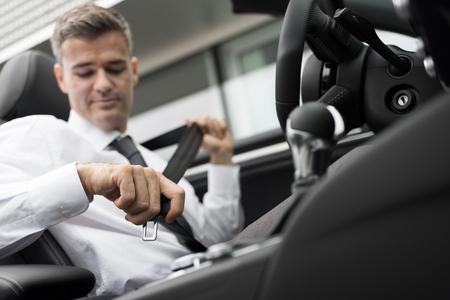 cinturón de seguridad: Hombre de negocios en su coche fijación del cinturón de seguridad, el concepto de conducción segura