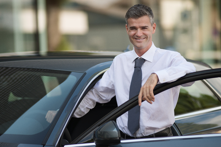 open car door: Businessman leaning on the car door and smiling at camera, dealership and business concept