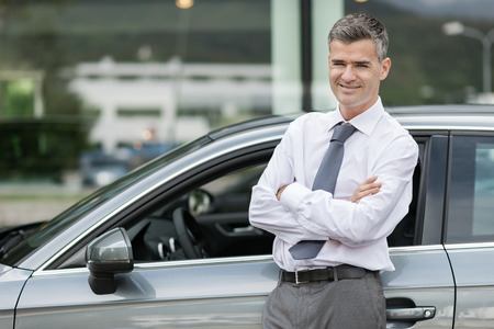 smiling businessman: Businessman smiling at camera and leaning against his new expensive car, dealership and business concept