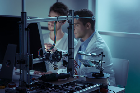 engineering and technology: Engineering students working in the lab and using a computer, 3D printer in the background, education and technology concept Stock Photo