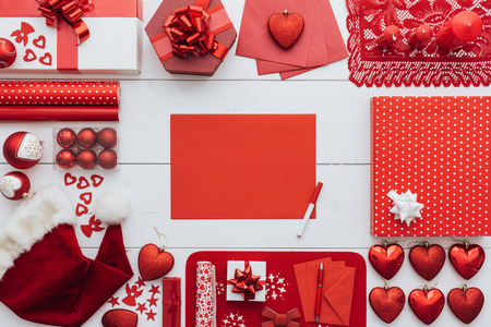 red sheet: Preparing for Christmas: frame composed of decorations and gifts with blank red sheet at center Stock Photo