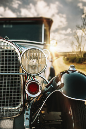 An old car along a country road at sunset, it is illuminated by the golden rays of the sun.