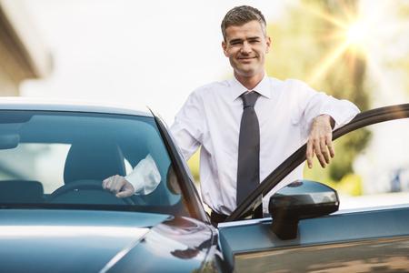 Hombre de negocios apoyado en la puerta del coche y sonriendo a la cámara, concesionario y concepto de negocio Foto de archivo
