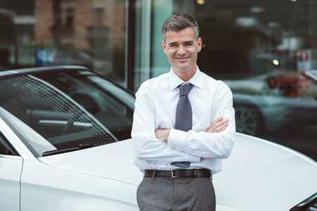 Confident businessman posing with his brand new car and smiling at camera Stock Photo