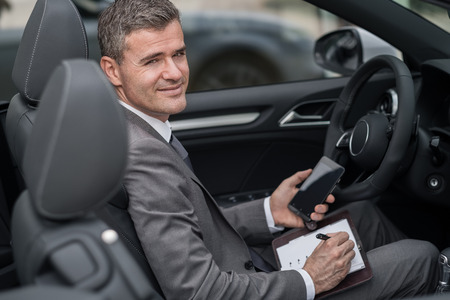 travelling salesman: Businessman sitting in his car, he is planning and scheduling meetings on his organizer and using apps on his smartphone Stock Photo