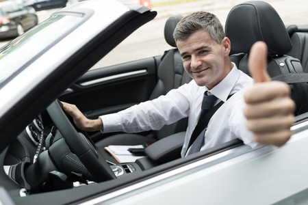 expensive car: Smiling successful man driving his new expensive car and giving a thumbs up Stock Photo