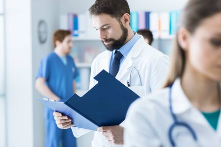 Confident doctor checking medical records on a clipboard in his office, medical staff on the background, healthcare concept Stock Photo