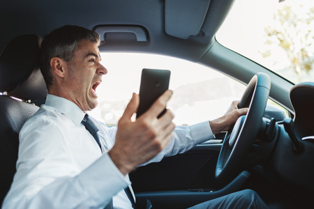 inattentive: Businessman using his smartphone while driving and having a car accident, he is shocked and screaming