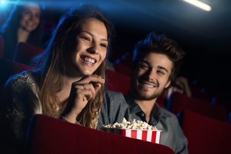 영화에서 젊은 부부 사람들이 배경에 앉아 영화를보고 미소