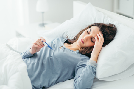 soreness: Woman with flu virus lying in bed, she is measuring her temperature with a thermometer and touching her forehead