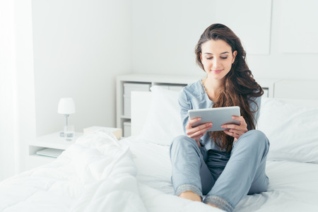 Young smiling woman sitting in the bed at home and connecting with a tablet, relax and leisure concept