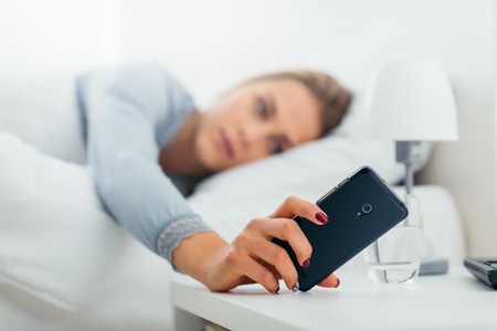 Young woman waking up in her bed and checking her phone