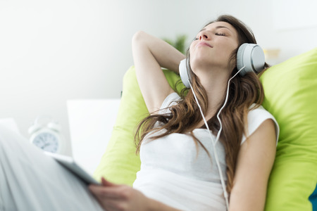 Beautiful young woman with headphones relaxing on the bed, she is listening to music using a tablet, chill out and leisure concept  Stock Photo