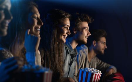 Grupo de amigos adolescentes en el cine viendo una película juntos y comiendo palomitas de maíz, el entretenimiento y el disfrute concepto Foto de archivo - 67097125