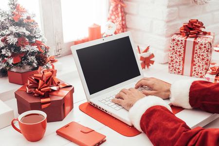 Kerstman bereidt voor Kerstmis en verbindt met een laptop, hij werkt thuis bij zijn bureau Stockfoto