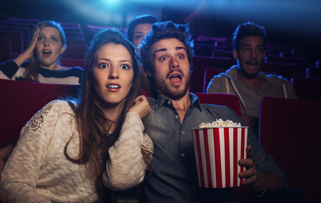 Young teenager couple at the cinema watching an horror movie Banque d'images