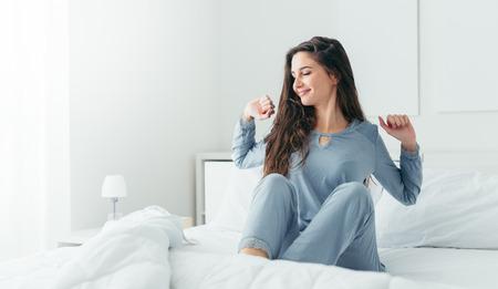 Belle femme se réveiller dans son lit dans la chambre, elle est l'étirement et souriant Banque d'images - 66975267