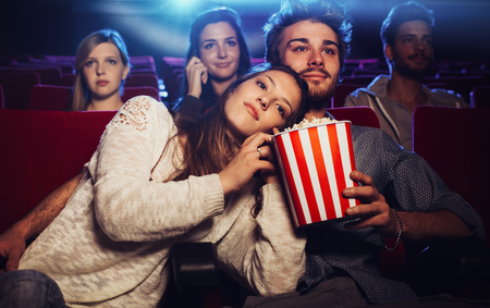 Jong houdend van paar in de bioscoop naar een film kijken, ze eten van popcorn haar vriendje Stockfoto