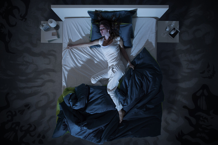 Nervous woman suffering from insomnia and lying in bed late at night, she is awake and restless, top view Reklamní fotografie - 66975290