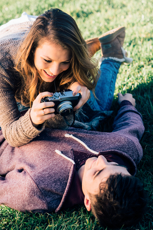 Playful young couple lying down on the grass and shooting with a camera, enjoyment and relationships concept photo