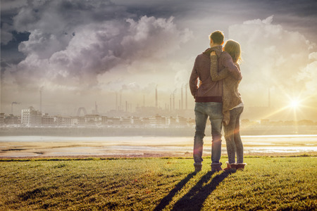 Happy romantic loving couple at the lake hugging and looking away, love and relationships concept