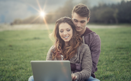 Smiling young couple sitting on the grass and using a laptop, she is chatting and social networking photo