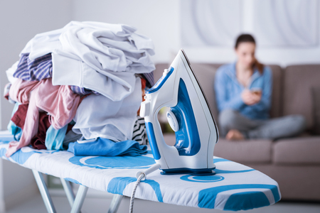 Lazy careless housewife on the couch at home and a pile of laundry on the ironing board on the foreground, boring household chores concept