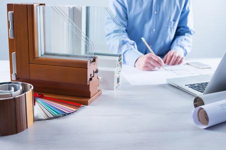 Windows gedeelte met driedubbele beglazing en houten frame en man werkt op een huis-project met de laptop op de achtergrond