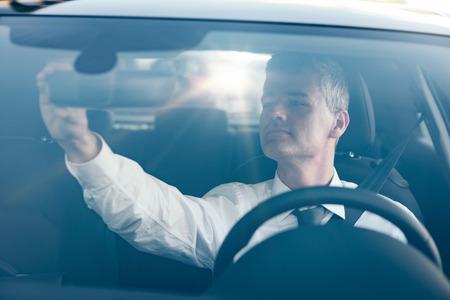 Hombre confía sentado en un coche y ajustar el espejo retrovisor Foto de archivo