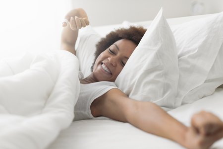 Beautiful woman waking up in her bed, she is smiling and stretching Фото со стока