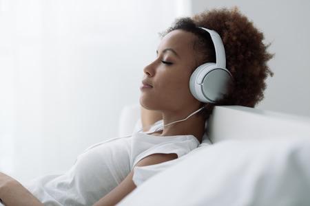 Hermosa mujer afroamericana joven que se relaja y que escucha la música usando los auriculares, que es en la cama Foto de archivo - 69275326