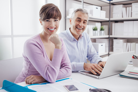 Succesful business team working at office desk, the man is typing with a laptop and the woman is smiling at camera, teamwork concept