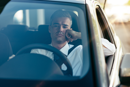 Pensive disappointed businessman sitting in his car and thinking with hand on chin Фото со стока