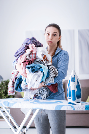 Annoyed housewife holding a pile of laundry that needs to be ironed, she is blowing her cheeks and staring at camera