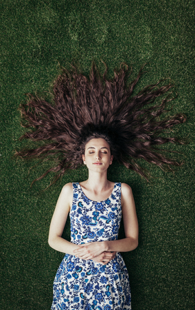 girl lying: Young girl lying on the grass with her long hair spread out, she is sleeping and relaxing Stock Photo