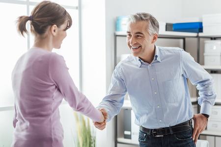 Gelukkig jonge kandidaat handen met haar werkgever schudden na een sollicitatiegesprek, de werkgelegenheid en zakelijke bijeenkomsten-concept Stockfoto
