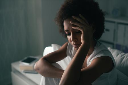 Droevige depressieve vrouw die lijdt aan slapeloosheid, zij zit in bed en raakt haar voorhoofd, slaapstoornis en stressconcept Stockfoto