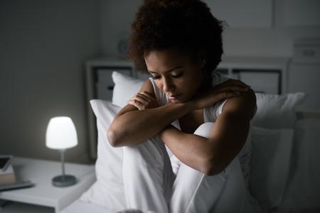 Sad depressieve vrouw zitten in haar bed 's avonds laat, ze is nadenkend en lijden aan slapeloosheid