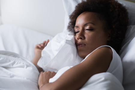 Young african woman sleeping in her bed at night, she is resting with eyes closed 스톡 콘텐츠