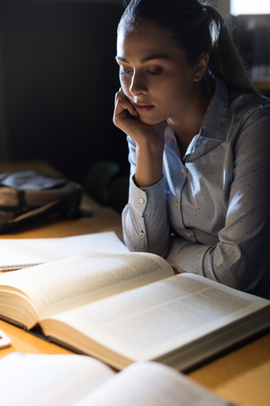 Efficient student girl reading late at night at the library, education and school concept